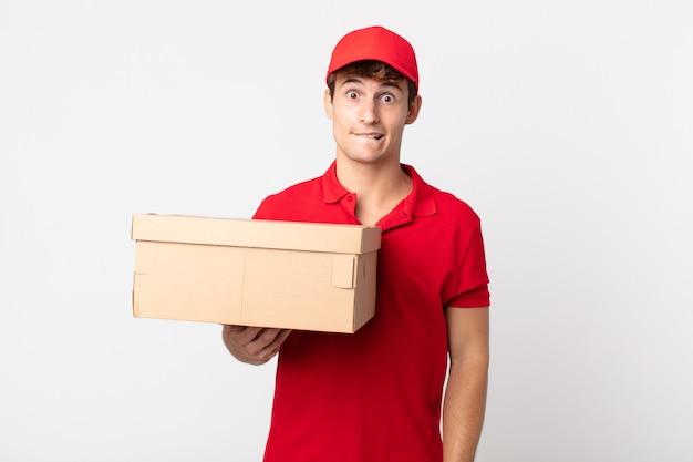 Jonge knappe man op zoek verbaasd en verward levering pakket dienstverleningsconcept.