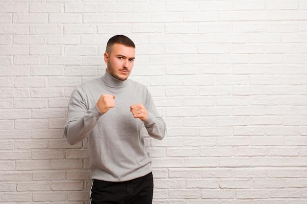Jonge knappe man op zoek zelfverzekerd, boos, sterk en agressief, met vuisten klaar om te vechten in boksen positie over muur