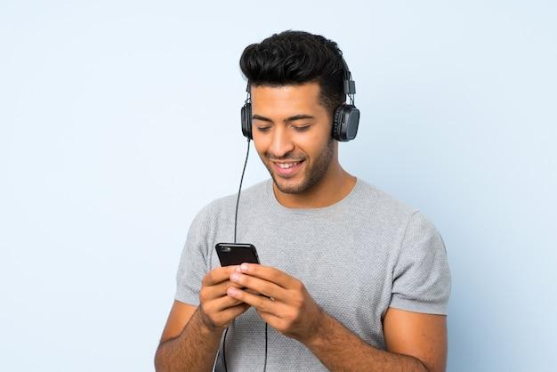 Jonge knappe man over geïsoleerde achtergrond met behulp van de mobiele telefoon met een koptelefoon