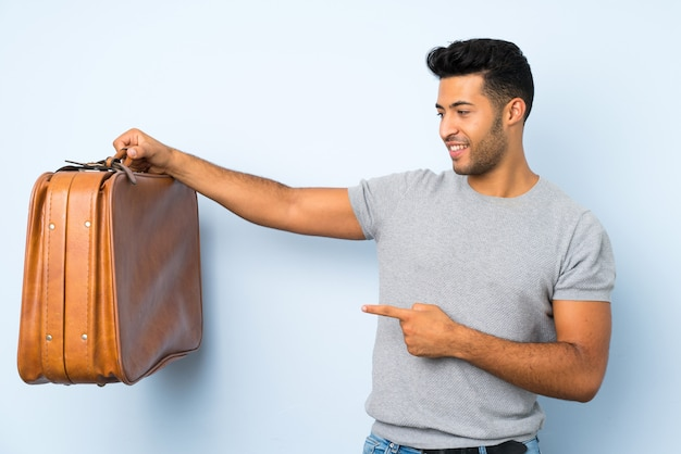 Jonge knappe man over geïsoleerde achtergrond met een vintage koffer