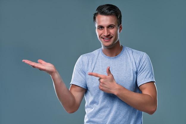 Jonge knappe man over geïsoleerde achtergrond verbaasd en glimlachend naar de camera terwijl hij met de hand presenteert en met de vinger wijst.