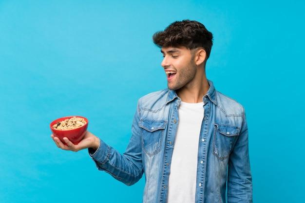 Jonge knappe man over geïsoleerde blauw met een kom ontbijtgranen