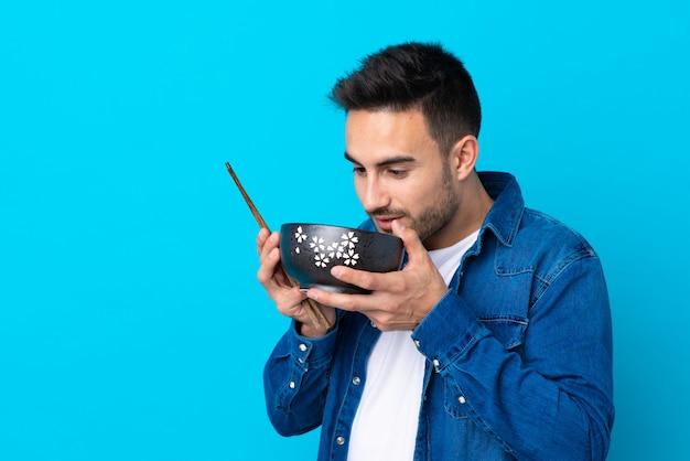 Jonge knappe man over geïsoleerde blauwe muur die een kom noedels met eetstokjes houdt en het eet