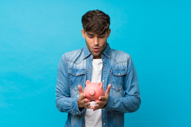 Jonge knappe man over geïsoleerde blauwe muur met een grote spaarpot