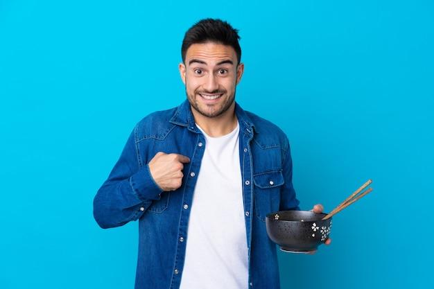 Jonge knappe man over geïsoleerde blauwe muur met verrassing gezichtsuitdrukking terwijl een kom noedels met stokjes