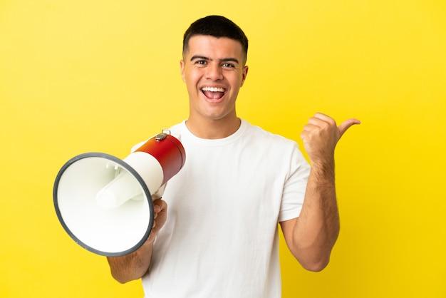 Jonge knappe man over geïsoleerde gele achtergrond die door een megafoon schreeuwt en naar de zijkant wijst