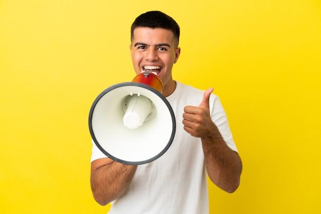 Jonge knappe man over geïsoleerde gele achtergrond die door een megafoon schreeuwt om iets aan te kondigen en met duim omhoog