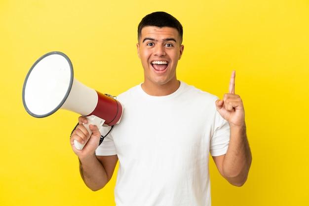 Jonge knappe man over geïsoleerde gele achtergrond die een megafoon vasthoudt en een geweldig idee naar boven wijst