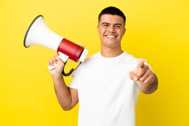 Jonge knappe man over geïsoleerde gele achtergrond die een megafoon vasthoudt en glimlacht terwijl hij naar voren wijst