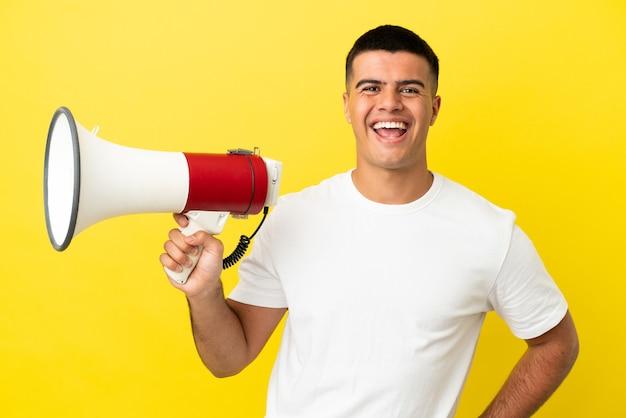 Jonge knappe man over geïsoleerde gele achtergrond die een megafoon vasthoudt en glimlacht