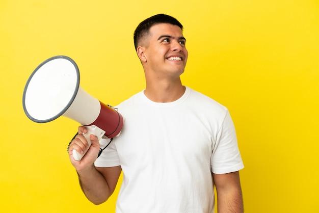 Jonge knappe man over geïsoleerde gele achtergrond die een megafoon vasthoudt en omhoog kijkt terwijl hij glimlacht