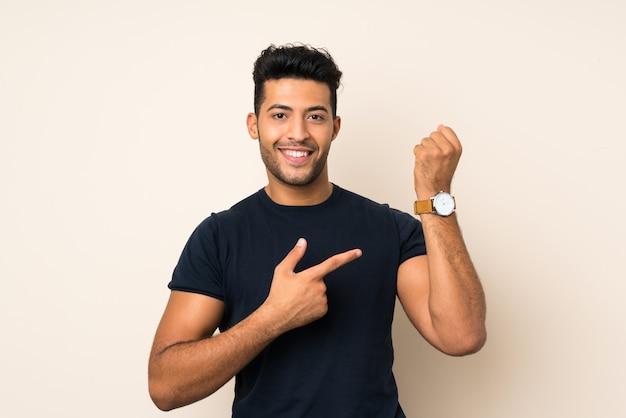 Jonge knappe man over geïsoleerde muur die het handhorloge toont
