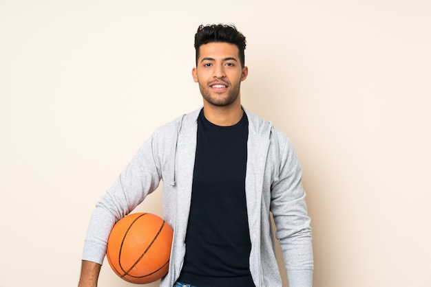Jonge knappe man over geïsoleerde muur met bal van basketbal