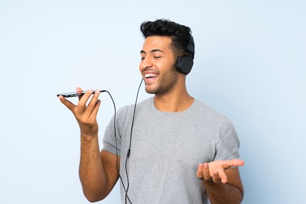 Jonge knappe man over geïsoleerde muur met behulp van de mobiele telefoon met koptelefoon en zingen