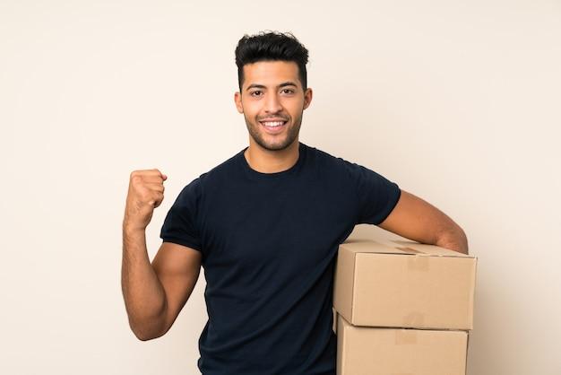 Jonge knappe man over geïsoleerde muur met een doos om het naar een andere site te verplaatsen
