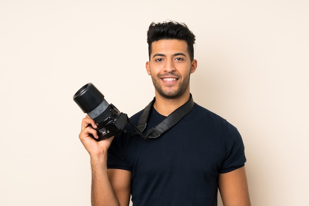 Jonge knappe man over geïsoleerde muur met een professionele camera