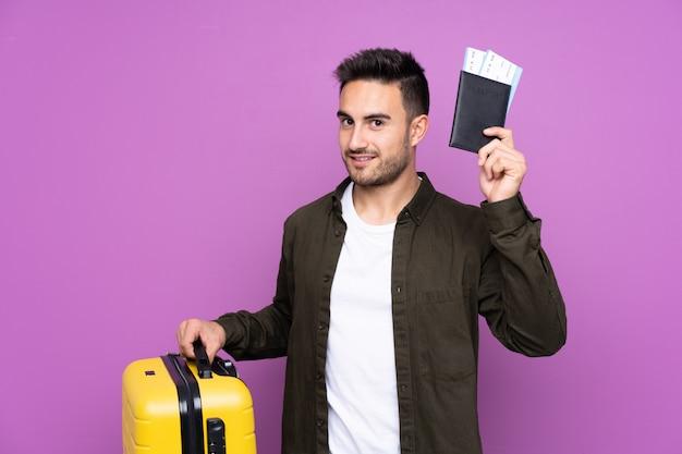 Jonge knappe man over geïsoleerde paarse muur in vakantie met koffer en paspoort