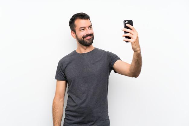 Jonge knappe man over geïsoleerde wit maken van een selfie