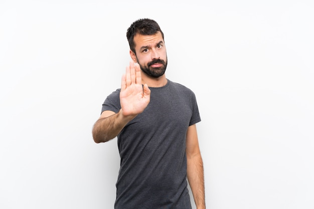 Jonge knappe man over geïsoleerde witte muur stop gebaar maken