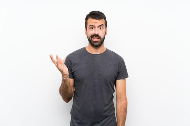 Jonge knappe man over geïsoleerde witte muur twijfels gebaar maken