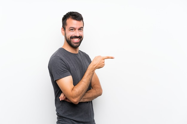 Jonge knappe man over geïsoleerde witte muur wijzende vinger aan de zijkant