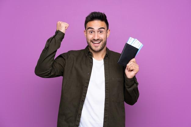 Jonge knappe man over paars gelukkig in vakantie met paspoort en vliegtuigtickets