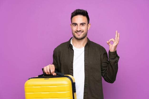 Jonge knappe man over paars in vakantie met reizen koffer en een hoed