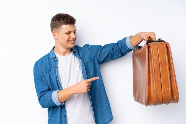 Jonge knappe man over wit met een vintage koffer