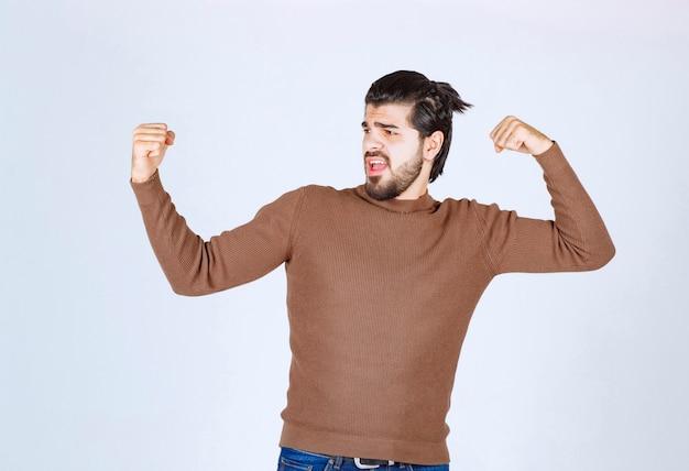 Jonge knappe man permanent en toont zijn spieren.