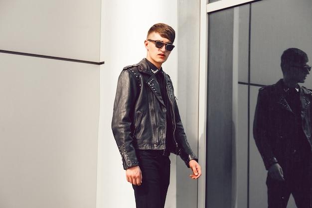 Jonge knappe man poseren in de buurt van moderne zakencentrum, stijlvolle leren puntige jas, zwarte spijkerbroek en zonnebril, brutale look.
