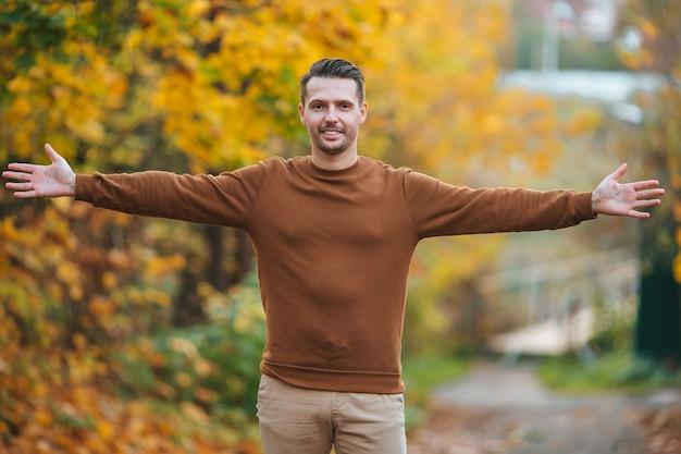 Jonge knappe man poseren in herfst park