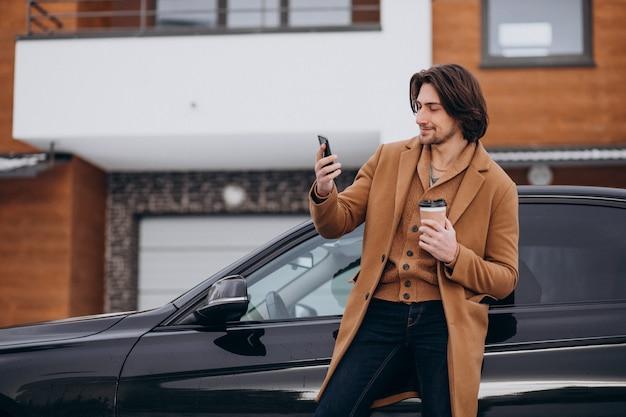 Jonge knappe man praten aan de telefoon door zijn auto