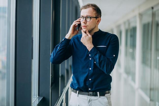 Jonge knappe man praten aan de telefoon op kantoor