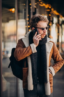Jonge knappe man praten over telefoon door de luchthaven