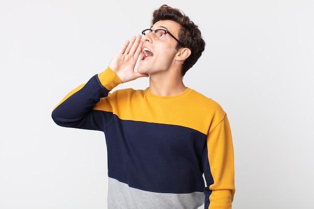Jonge knappe man profielweergave, blij en opgewonden kijkend, schreeuwend en bellend om ruimte aan de zijkant te kopiëren