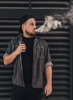 Jonge knappe man rook met vape in de buurt van zwarte muur