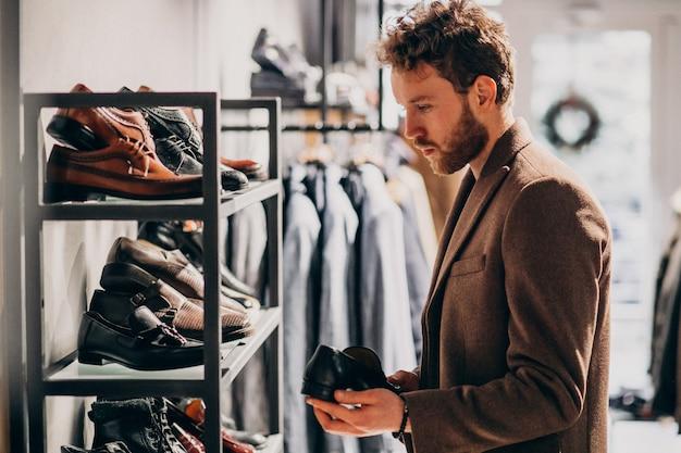 Jonge knappe man schoenen kiezen in een winkel