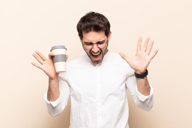 Jonge knappe man schreeuwen in paniek of woede, geschokt, doodsbang of woedend, met de handen naast het hoofd