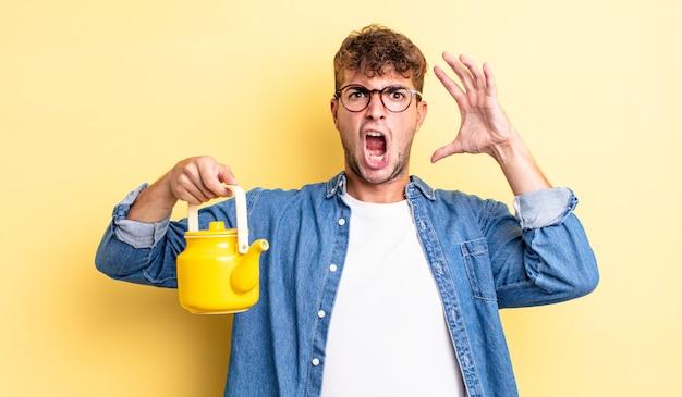 Jonge knappe man schreeuwen met handen omhoog in de air.teapot concept