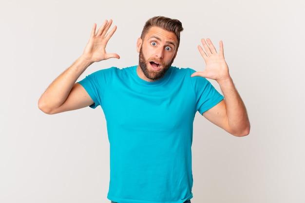 Jonge knappe man schreeuwen met handen omhoog in de lucht. fitnessconcept