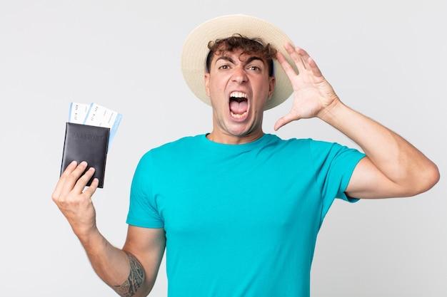 Jonge knappe man schreeuwen met handen omhoog in de lucht. reiziger met zijn paspoort