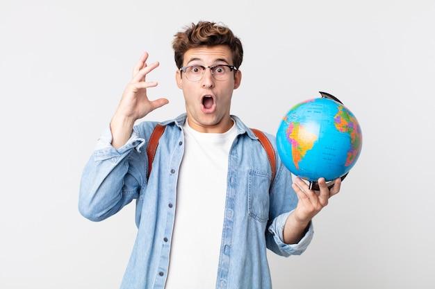 Jonge knappe man schreeuwen met handen omhoog in de lucht. student met een wereldbolkaart