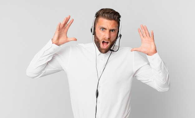 Jonge knappe man schreeuwen met handen omhoog in de lucht. telemarketing concept