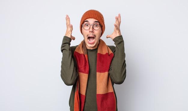 Jonge knappe man schreeuwen met handen omhoog in de lucht. winterkleren concept