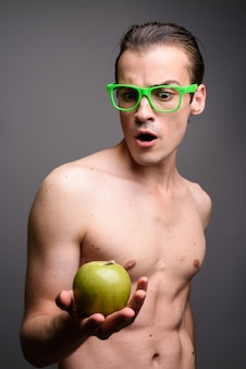 Jonge knappe man shirtless bedrijf appel op grijs
