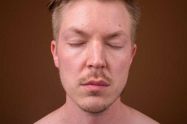 Jonge knappe man shirtless tijdens het verzorgen