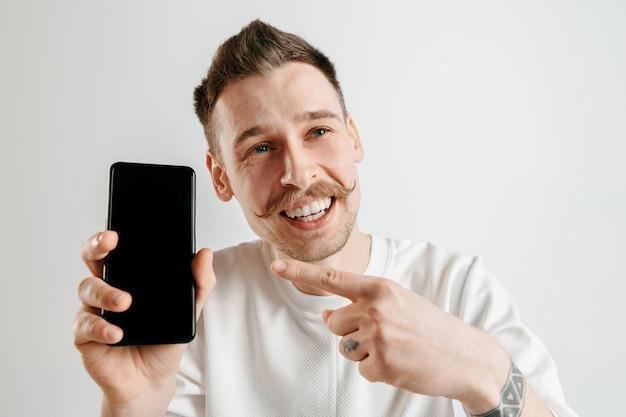 Jonge knappe man smartphonescherm tonen over grijze ruimte met een verrassingsgezicht