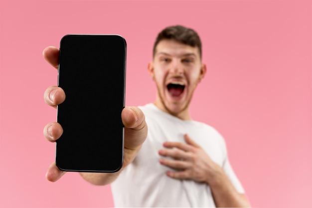 Jonge knappe man smartphonescherm tonen over roze ruimte met een verrassingsgezicht