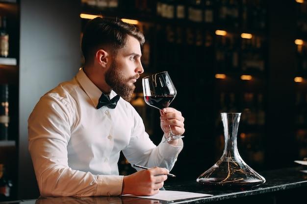 Jonge knappe man sommelier rode wijn proeven in de kelder