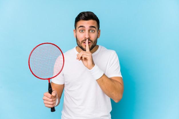 Jonge knappe man spelen badminton geïsoleerd houden van een geheim of vragen om stilte.